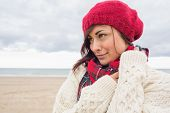 stock photo of pullovers  - Close up of a young woman in knitted hat and pullover looking away on the beach - JPG