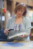 Mature female librarian scanning book standing behind the desk