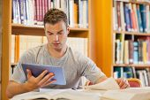 Attractive focused student using tablet and turning page in library