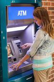 Pretty happy student withdrawing cash at an ATM