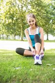 Smiling active brunette tying her shoelaces in a park on a sunny day