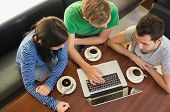 stock photo of canteen  - Overhead view of three students using laptop while having coffee at  the coffee shop - JPG