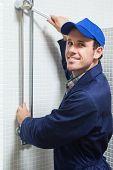 Smiling plumber repairing shower head in public bathroom