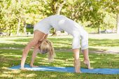 Fit young woman doing crab yoga pose in a park