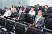 Image of business people sitting in rows at seminar