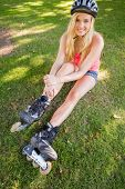 Casual content blonde wearing roller blades and helmet in a park