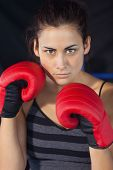 Close-up portrait of a beautiful young woman in red boxing gloves in the ring