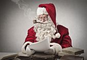 Santa Claus smoking a pipe and reads gifts requests