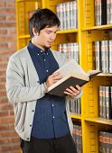 Male student reading book while standing by shelf in college library