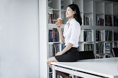 Smiling young businesswoman holding coffee and sitting on table