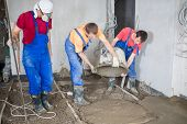 Three workers pour out the mortar of cement from a bucket to pour the floor