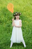Little cute girl in white holds orange butterfly net on green meadow.