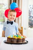 Portrait of happy boy standing in front of birthday cake at home