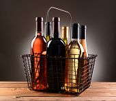 A wire shopping basket filled with assorted wine bottles. The basket is sitting on a rustic wooden table with a light to dark gray spot background.