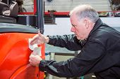 Mechanic, branding a forklift by placing a sticker on the side - applying the final touch