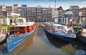 Colorful Pleasure boats stand moored on Damrak Canal pier in historical center of Amsterdam
