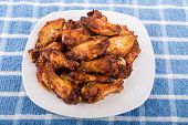 foto of mesquite  - Fried chicken wings with mesquite sauce on a white plate - JPG
