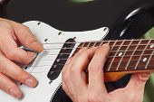 Rock guitarist put fingers for chords on electric guitar