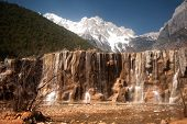 White Water River Waterfall In Lijiang Near Jade Dragon Snow Mountain.