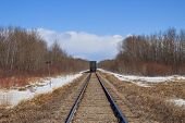 image of railcar  - Rail car on a railroad track lined by bare trees - JPG