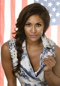 Beautiful exotic young woman wearing denim - hair in pony tail - USA American flag in background