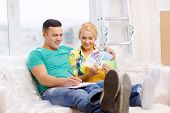 moving, home and couple concept - smiling couple looking at color samples in new home