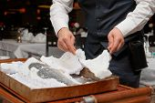 Waiter is carving fish baked in salt crust by restaurant table