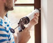 stock photo of hermetic  - Man applying silicone sealant with caulking gun - JPG