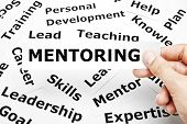 stock photo of mentoring  - Hand holding a piece of paper with the word Mentoring on it - JPG