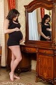Pregnant Woman Stands Before Dressing Table.