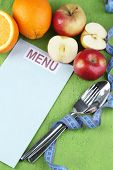Cutlery tied with measuring tape and menu with fruits on wooden background