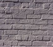 stock photo of gey  - surface of the wall with bricks plastered and painted illuminated by sunlight - JPG