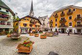 HALLSTATT, AUSTRIA - 21 JUNE 2014: Town square in Hallstatt, Austria. Hallstatt is historical village located in Austrian Alps at the Hallstatter lake and promoted by UNESCO World Heritage region.