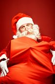 Portrait of happy Santa Claus with gigantic sack full of gifts looking at camera