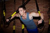 Young man doing exercises for arm muscles in gym