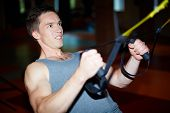Young man making great effort while doing difficult exercise in sports gym