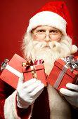 Happy Santa Claus with giftboxes looking at camera