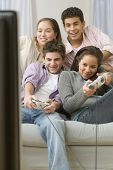 Four teenagers on couch playing video games