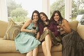 Portrait of three women sitting on couch with wine glasses