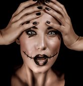 Closeup portrait of terrifying witch with spooky painted face and open mouth isolated on black background, Halloween holiday concept
