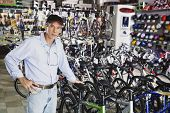 foto of flogging  - Portrait of man standing in bike shop - JPG