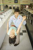 Couple dancing in a laundromat