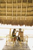 Couple drinking beer at a table underneath thatch roof