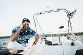 Young man talking on his cell phone and using a laptop on a boat