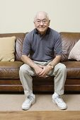 Portrait of elderly man sitting on couch