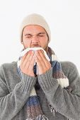 Portrait of young man in warm clothing sneezing over white background