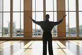 Businessman standing in sunlit room with arms outstretched