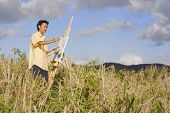 Asian man painting at easel outdoors