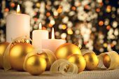 Warm Christmas glitter bokeh background with candles, baubles and ribbons