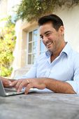 Mature man on week-end working from home with laptop